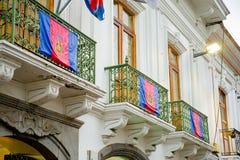 QUITO, EQUADOR NOVEMBRO, 28, 2017: Construção branca bonita com alguns glags que penduram de um balcão no centro histórico Imagem de Stock Royalty Free