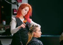 QUITO, EQUADOR - OUTUBRO, 25, 2017: Feche acima de um cabeleireiro que seca a mulher loura que usa um secador de cabelo e uma esc imagens de stock