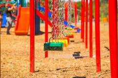 QUITO, EQUATEUR - 8 AOÛT 2016 : Le terrain de jeu public coloré balance pendre des chaînes en métal, glissière rouge à l'arrière- Photos stock