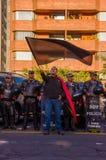 Quito, Equateur - 7 avril 2016 : Drapeau de ondulation de protestataire se tenant devant la police anti-émeute donnant sur d'anti Photo stock