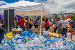 Quito, Equateur - avril, 17, 2016 : Les citoyens non identifiés de Quito fournissant le secours en cas de catastrophe arrosent po Photographie stock libre de droits