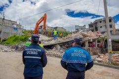 Quito, Equateur - avril, 17, 2016 : Police métropolitaine regardant la maison détruite par tremblement de terre avec des sauveteu Photos stock