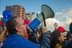 Quito, Equateur - 7 avril 2016 : Protestataire inconnu d'opposition avec le mégaphone entouré par les personnes, la police et les Photographie stock libre de droits