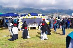 QUITO, EQUATEUR - 7 JUILLET 2015 : Nonnes priant pour le pape Francisco, peu d'autel dans une tente avec des fleurs et ballons da Photographie stock libre de droits
