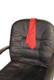 Quitting Time. Red mens neck tie draped over the back of a black office desk chair iso Royalty Free Stock Photos