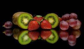 Quivi, morangos e uvas em um fundo preto Fotos de Stock Royalty Free