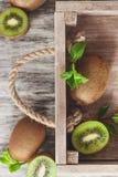 Quivis e folhas de hortelã verdes na bandeja de madeira imagem de stock royalty free