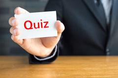 Quiz, message on white card and hold by Stock Photography