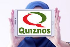 Quiznos fast food restaurant logo. Logo of Quiznos fast food restaurant on samsung tablet holded by arab muslim woman. Quiznos, is a franchised fast-food stock images