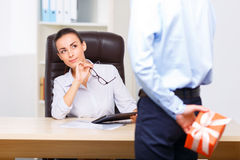 Quizzical office manager sitting at the desk Royalty Free Stock Photo