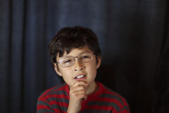 Quizzical young boy in glasses Royalty Free Stock Image