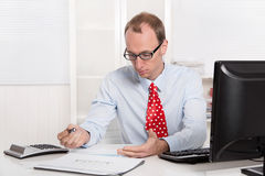 Quizzically engineer or specialist in shirt and tie sitting at d Stock Images