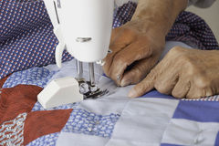 Qulter machine quilting patriotic quilt. Close up of a quilter removing a safety pin prior to sewing colorful fabric to make a patriotic quilt Stock Images