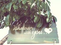 Quoi qu'avec vous écrit sur le message romatic en bois d'amour avec le coeur à l'arbre Photos libres de droits