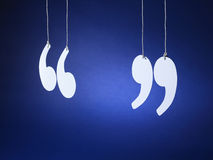 Quotation marks inverted commas - Stock Image. Shot of quotation marks or inverted commas cut out from white card and suspended on string on a blue background royalty free stock images