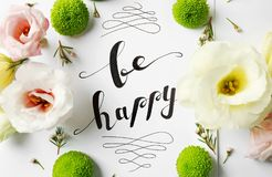 Quote `Be happy` written on paper with flowers on white background. Top view