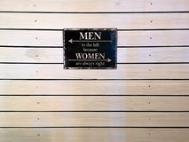 Quote frame on a wood wall - Men to the left because women are always right royalty free stock images