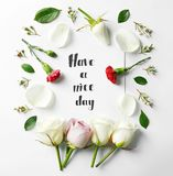 Quote `Have a nice day` written on paper with petals and flowers. Top view royalty free stock image