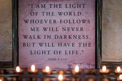 Quote from the Psalm of John in church. Memorial candles burning in church in front of a wall plaque with bible verse or passage from the Psalm of John stock image