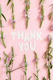 Quote Thank You made of letters cut out of paper. Pattern made of wild flowers stock photo