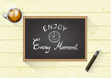 Quote Typographical on Chalkboard Background,  design, Hand drawn lettering. Enjoy Every Moment with chalkboard lettering. Pen and a cup of hot coffee Stock Photo