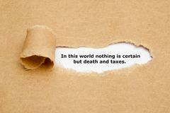 In This World Nothing Is Certain But Death And Taxes. Quote In this world nothing is certain but death and taxes, appearing behind ripped brown paper royalty free stock images