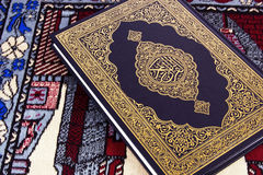 Qur'an over Muslim prayer carpet Stock Image