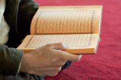 Quran. A man reading the quran stock photos