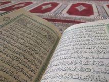 Quran auf eleganten Perserteppichen - der arabische Text mit englischer Übersetzung Lizenzfreies Stockbild