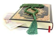 Quran cerrado de golpe con moneda iraní Imagenes de archivo