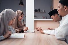 Quran de la lectura de la familia o libro sagrado musulm?n del Islam junto imágenes de archivo libres de regalías