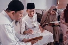 Quran de la lectura de la familia o libro sagrado musulm?n del Islam junto imagenes de archivo