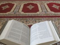 Quran on elegant Persian rugs - the Arabic text with English translation. Quran on a Persian rug stock photos