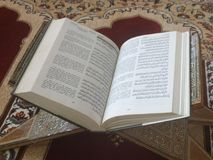 Quran on elegant Persian rugs - the Arabic text with English translation. Quran on a Persian rug stock photo
