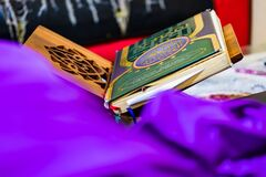Quran, the Muslim Holy Book, on wooden book stand at home