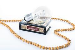 Quran med radbandet med lampan - helig bok av muselmaner - Koranen - vit bakgrund f?r quran arkivbilder