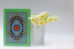 Quran mit Narzissen auf weißem Hintergrund Ramadan-Konzept Lizenzfreies Stockbild