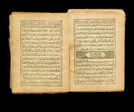 Quran. Opened old Quran on black background Royalty Free Stock Photography