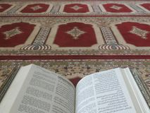 Quran on elegant Persian rugs - the Arabic text with English translation. Quran on a Persian rug royalty free stock images