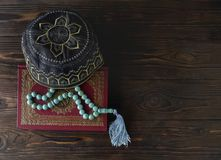 Islamic book Koran with rosary beads and muslim hat on wooden background. Islamic concept with copy space. Quran with rosary on wooden background royalty free stock image