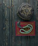 Islamic book Koran with rosary beads and muslim hat on wooden background. Islamic concept with copy space. Quran with rosary on wooden background stock image