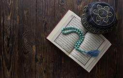 Islamic book Quran with rosary beads and muslim hat on wooden background. Islamic concept with copy space. Quran with rosary on wooden background stock image