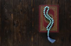 Koran with rosary beads on wooden background. Islamic concept with copy space. Quran with rosary on wooden background stock images