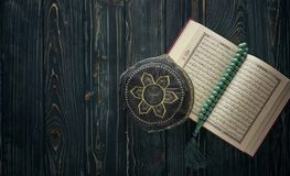 Open Koran with rosary beads and muslim hat on wooden background. Islamic concept with copy space. Quran with rosary on wooden background stock photography