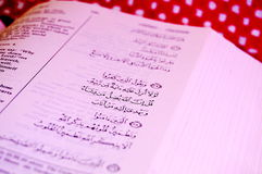 Quran Sura. Up close of the book of Quran in English and Arabic with a kiffiyeh in the background Royalty Free Stock Images