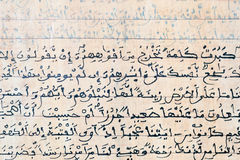 Quran verses written on a wood board -close up-. Quran verses written by hand on a wooden board, and to be specific, this is the beginning of chapter 18 called Royalty Free Stock Images
