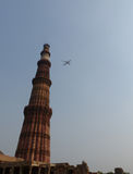 Qutb Minar, Delhi. The tallest brick minaret in the world - with passing airplane Stock Photography