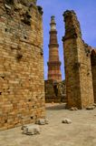 Qutub minar and ruins. Qutub Minar (Delhi, India) is the tallest brick minaret in the world. The tower has been built in XII-XIII centuries Stock Photo