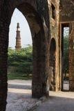 Qutub Minar som sedd fördärvar igenom av den arkeologiska mehraulien parkerar Arkivfoton