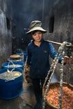 Quy Nhon,越南- 2016年10月22日:处理在鱼市上的海鲜在Quy Nhon,越南南方 妇女运载煮沸的se篮子  图库摄影